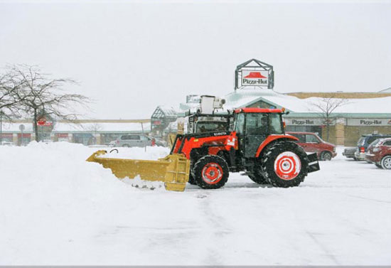 tractor removing snow in parking lot